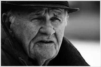 Orta yaşlı ve düzgün giyimli bir adam sessizce kafeye girerek köşedeki masaya oturur.
